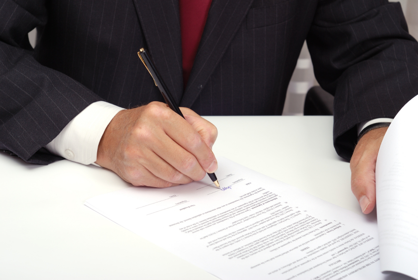 Businessman with black pen signing contract.